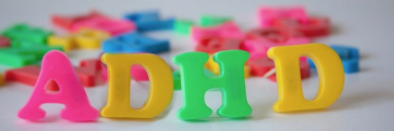 Pink, yellow, and green plastic magnetic letters arranged to spell ADHD